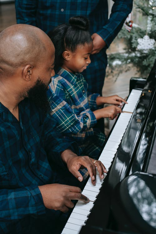 Black father with son and daughter playing piano at home