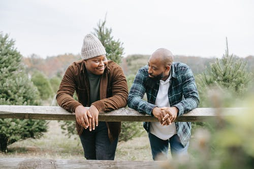 African American teen man having conversation with dad leaning on fence standing against green trees and looking at each other