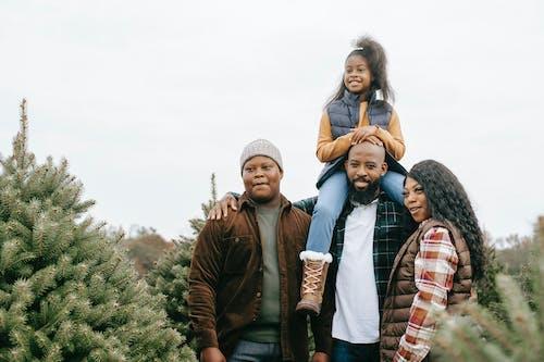Cheerful black family choosing fir tree together