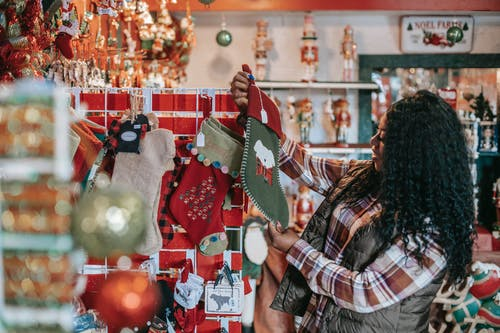 Side view of smiling African American female with Xmas sock in shop with decorative baubles and gifts
