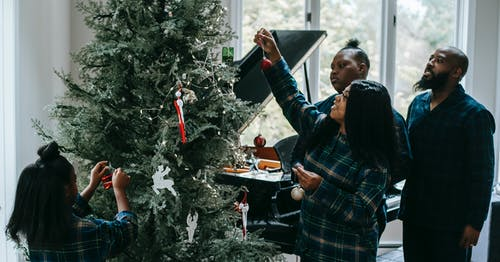 African American family gathering around fir tree and hanging toys on branches during Christmas celebration