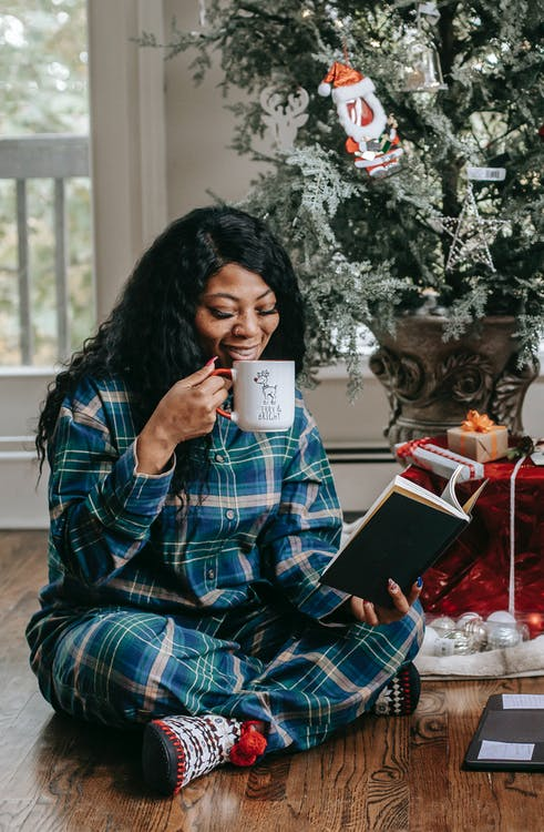 Smiling black woman reading book and drinking hot coffee