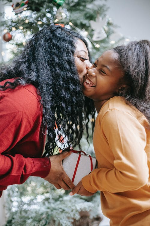 Side view of smiling African American mum kissing cheerful daughter while giving Christmas gift box