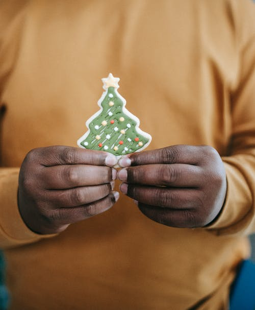 Black man with gingerbread in form of Christmas tree