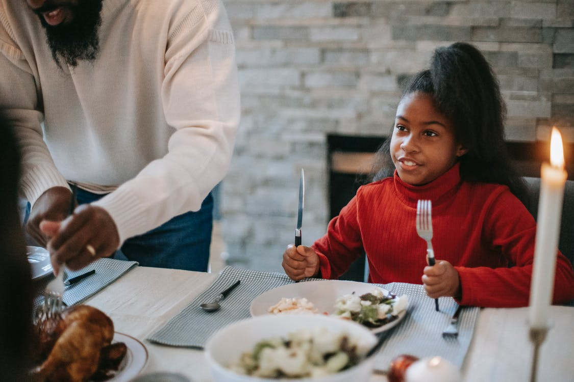 Smiling African American girl sitting at table near father cutting meat during festive dinner with burning candles