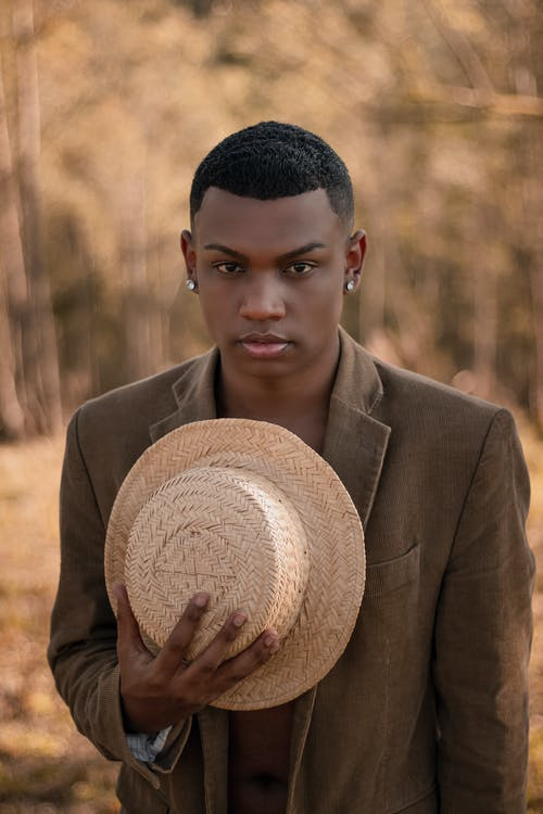Young African American male in stylish jacket with earrings and straw hat in hands looking at camera