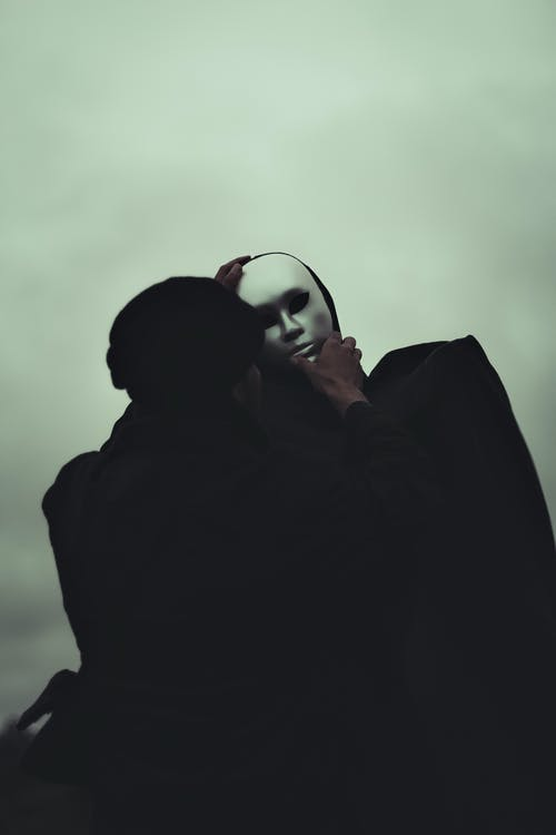 Black and white of anonymous male in black outfit covering face of faceless person with white mask