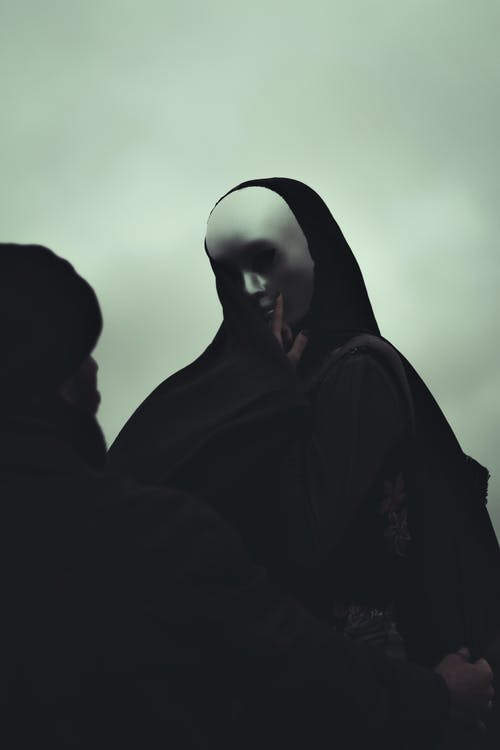 Black and white of anonymous man and anonymous person in white mask touching covered face