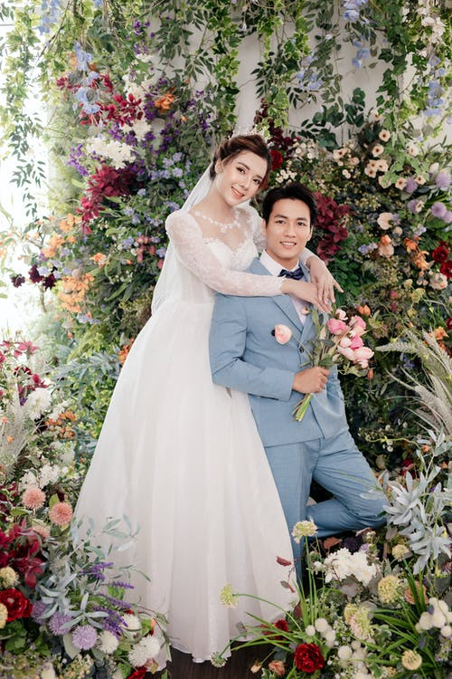 Full body content Asian bride wearing chic wedding dress standing behind smiling groom in studio decorated with flowers while hugging grooms shoulders and looking at camera happily