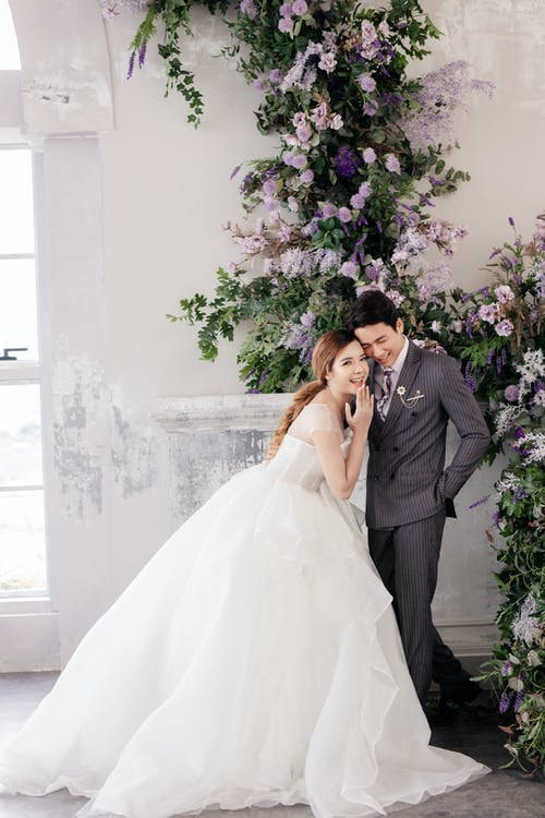 Joyful Asian newlywed couple standing in light studio