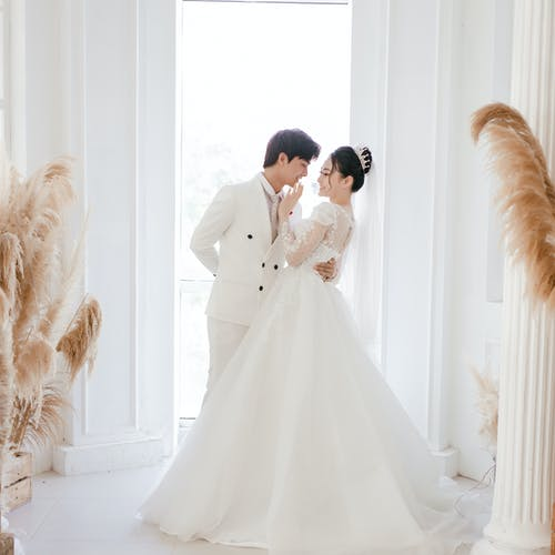 Elegant Asian newlyweds embracing in modern light mansion