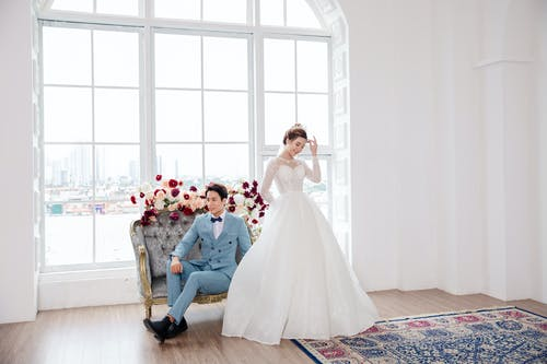 Full length happy Asian bride wearing chic  white dress standing near groom resting on classy sofa in light spacious studio
