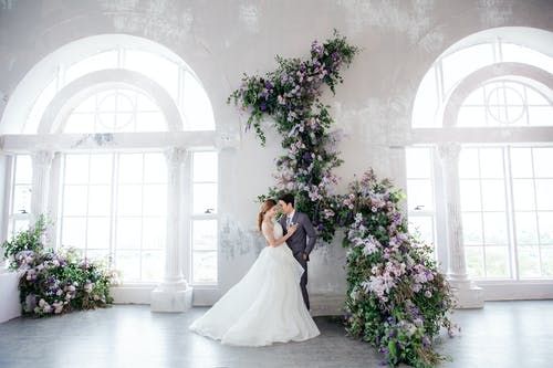 Side view full body romantic newlywed Asian couple wearing luxurious gowns hugging tenderly during wedding photo session in spacious light studio decorated with fragrant flowers