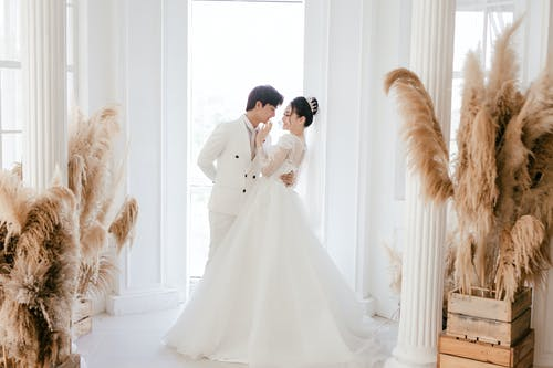 Side view full length cheerful young Asian bride touching grooms lips while hugging and looking at each other in fancy wedding studio