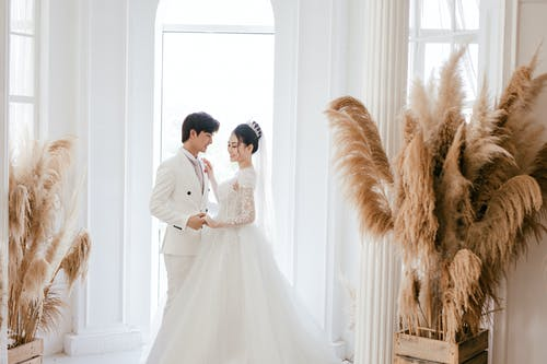 Side view positive newlywed Asian couple wearing classy gowns holding hands and dancing in fancy wedding studio