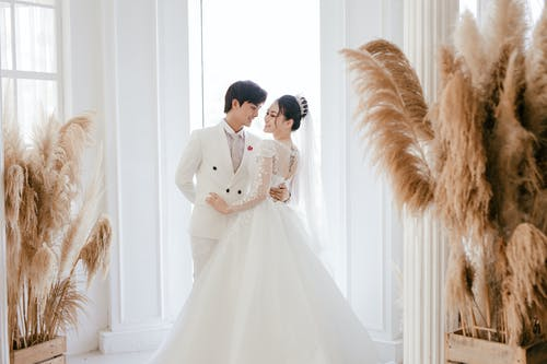 Romantic newlywed Asian couple wearing elegant white gowns hugging and looking at each other while standing in stylish studio decorated with plants