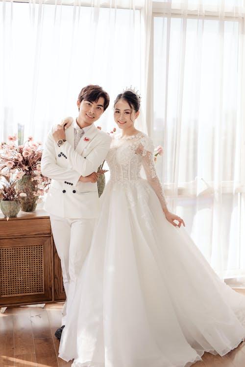 Cheerful Asian newlyweds standing in stylish studio