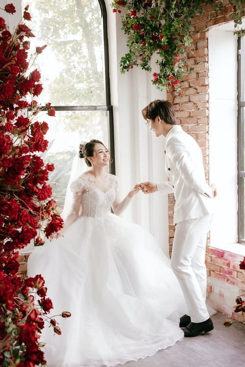 Full length cheerful newlywed Asian couple wearing elegant white wedding gowns holding hands and looking at each other with love
