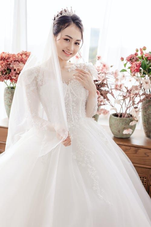 Gorgeous Asian bride standing in wedding studio