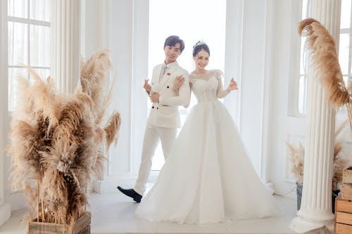 Happy Asian newlyweds standing in luxury wedding studio