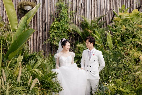 Positive Asian newlywed couple standing in greenery