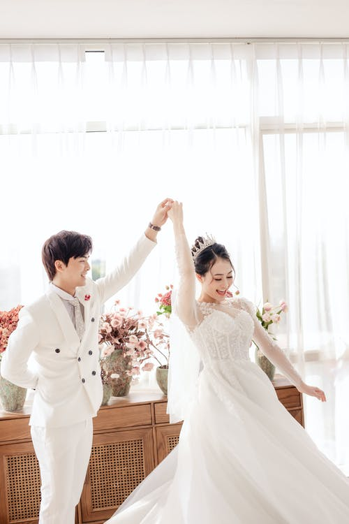 Happy ethnic newlywed couple dancing at wedding ceremony