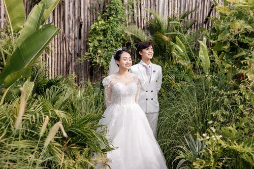 Asian bride and groom in wedding clothes in green garden
