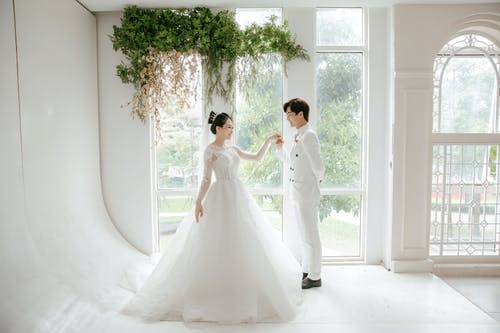 Positive ethnic newlywed couple standing near panoramic window