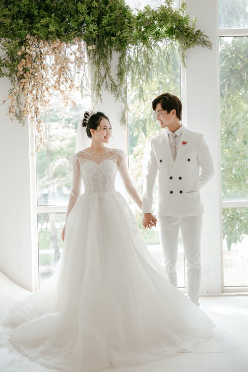 Full body of young Asian couple wearing white wedding outfits holding hands and smiling to each other