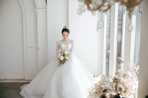 Happy ethnic bride in dress and crown with bouquet