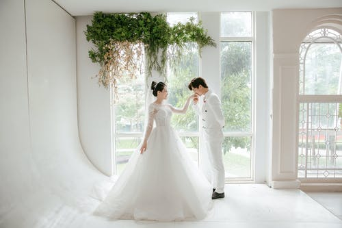 Side view full body of ethnic groom kissing hand of bride while having wedding day in white room