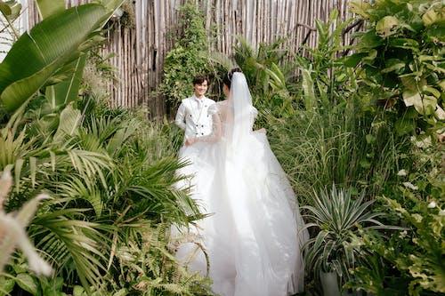 Bride in white wedding fluffy dress walking towards smiling Asian groom in green garden