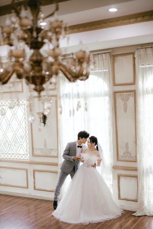 Elegant Asian newlyweds in spacious ballroom