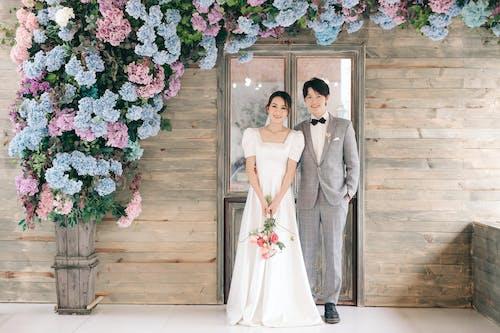Woman in White Wedding Dress Beside Man in Gray Suit