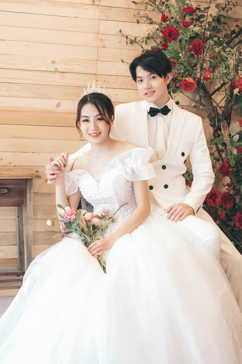 Woman in White Wedding Gown Beside Man in Black and White Tuxedo