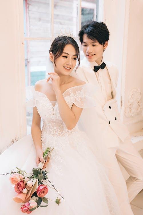 Woman in White Wedding Dress Beside Man in Black Tuxedo