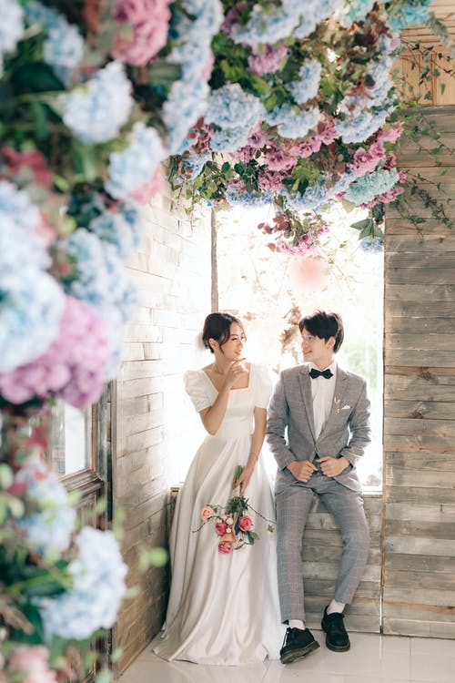 Man in Gray Suit Kissing Woman in White Wedding Dress