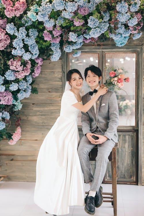 Man in Gray Suit Jacket Hugging Woman in White Wedding Dress