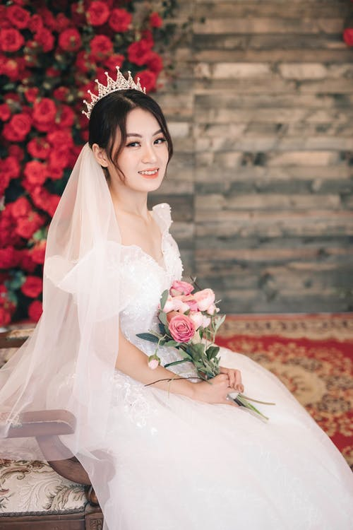 Woman in White Wedding Dress Holding Bouquet of Red Roses