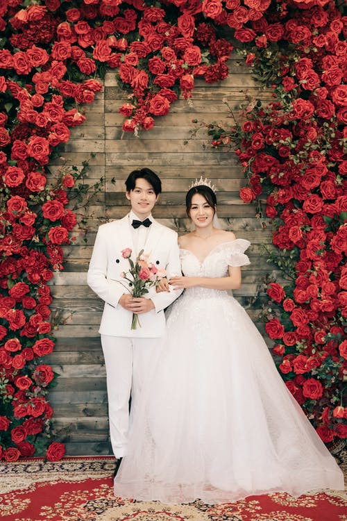 Bride and Groom Standing on Red Flower Field