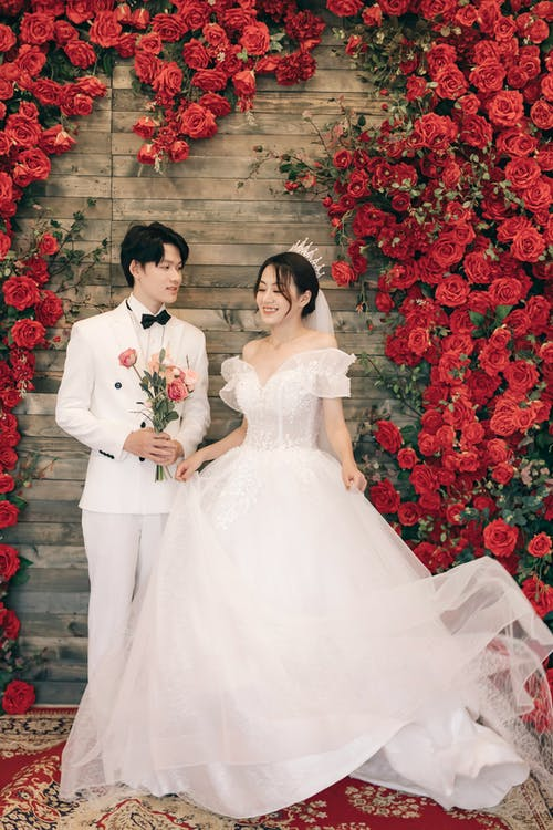 Woman in White Wedding Dress Holding Man in Black Suit