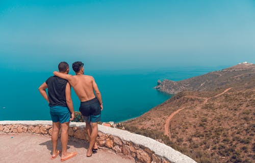 Two Man Standing on Mountain Cliff With Ocean View