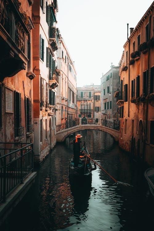 Boat on River Between Buildings
