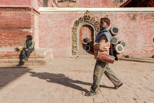 Full body of ethnic man carrying traditional musical instruments while walking on block stone pavement along street near brick building in bright sunlight