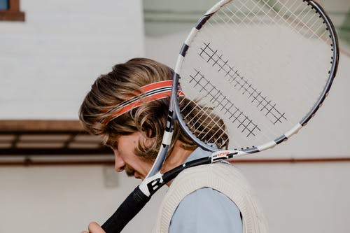 Person Holding White and Black Tennis Racket