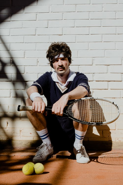 Man in Blue and White Striped Polo Shirt Holding White and Red Tennis Racket