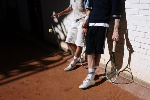 Man in Blue Long Sleeve Shirt and White Shorts Holding Tennis Racket