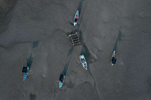 Boats placed on wet sandy coast