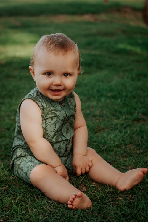 Cute toddler child resting on grass lawn in garden