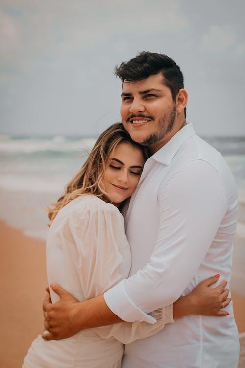 Happy couple embracing on sandy beach against sea